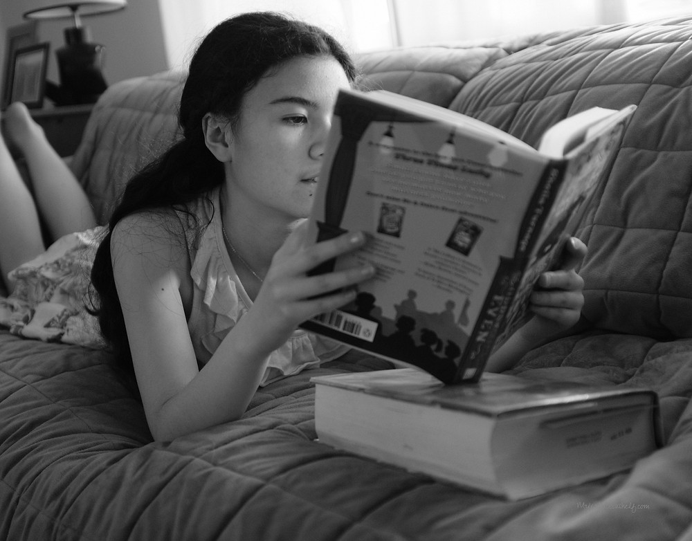 Top-10-Tips-for-Reading-Success Girl reading books laying down on couch