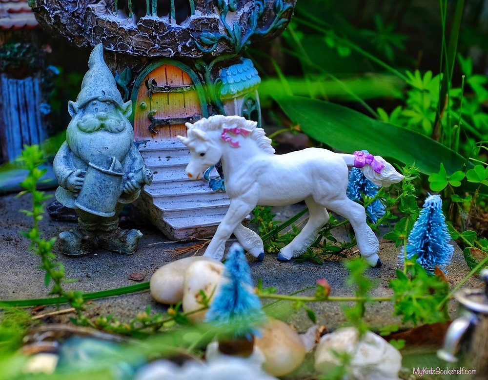Fairy garden with garden gnome, unicorn, bottle brush trees and castle in the background
