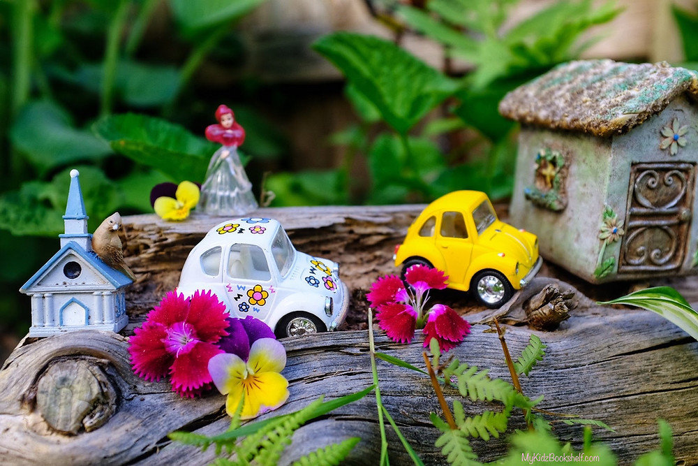 log with fairy cottage, mini steepled church, Volkswagen bug mini cars and flowers