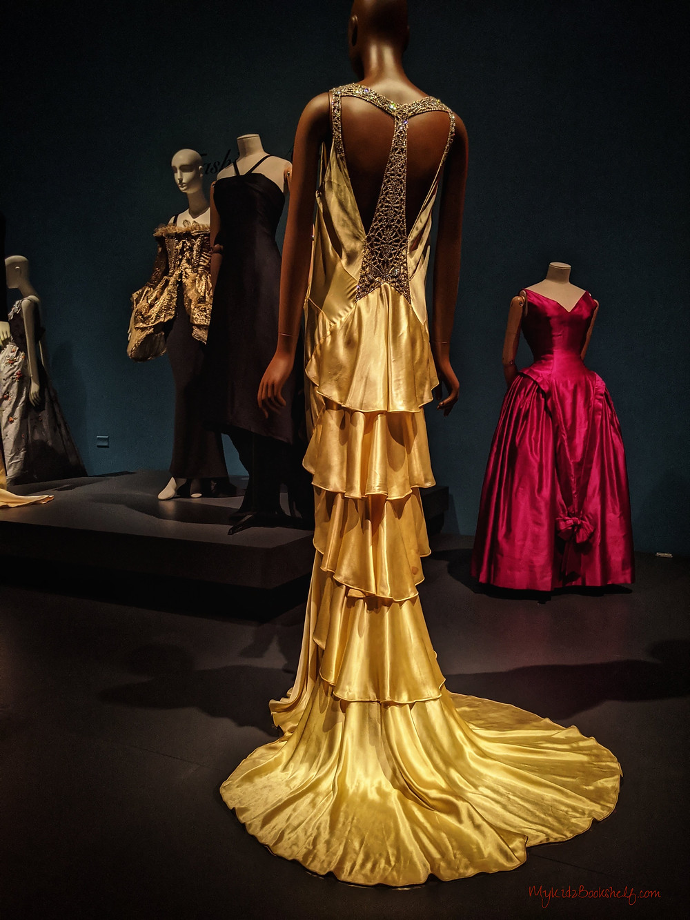 long-gold-open-backed-gown-as-part-of-paris-fashion-with-other-dresses-int-the-background