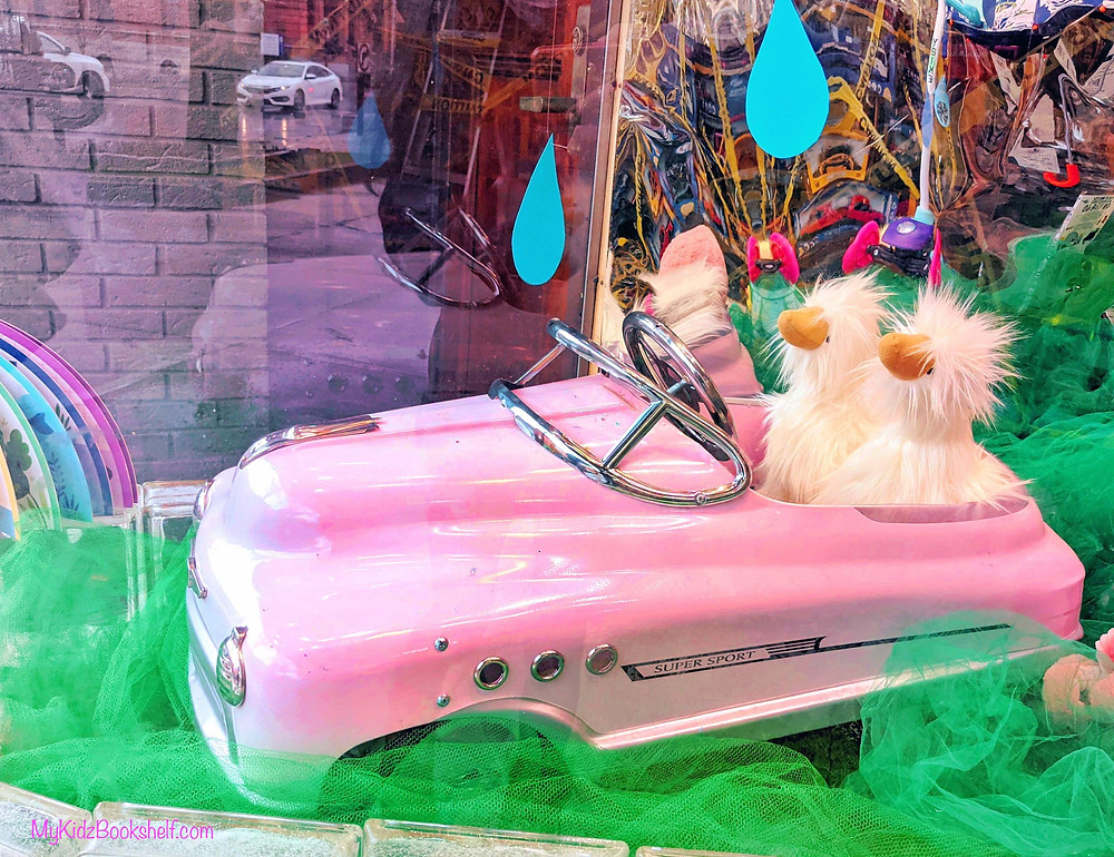 pink toy car with chicks in window display