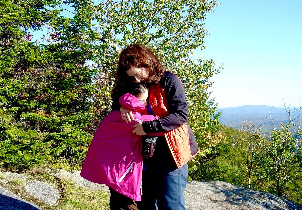 mother-daughter-hugging-at-top-of-mountain-after-long-hike