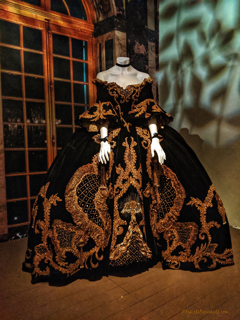 elaborate-French-gown-off-the-shoulder-wide-black-skirt-with-much-gold-detailing