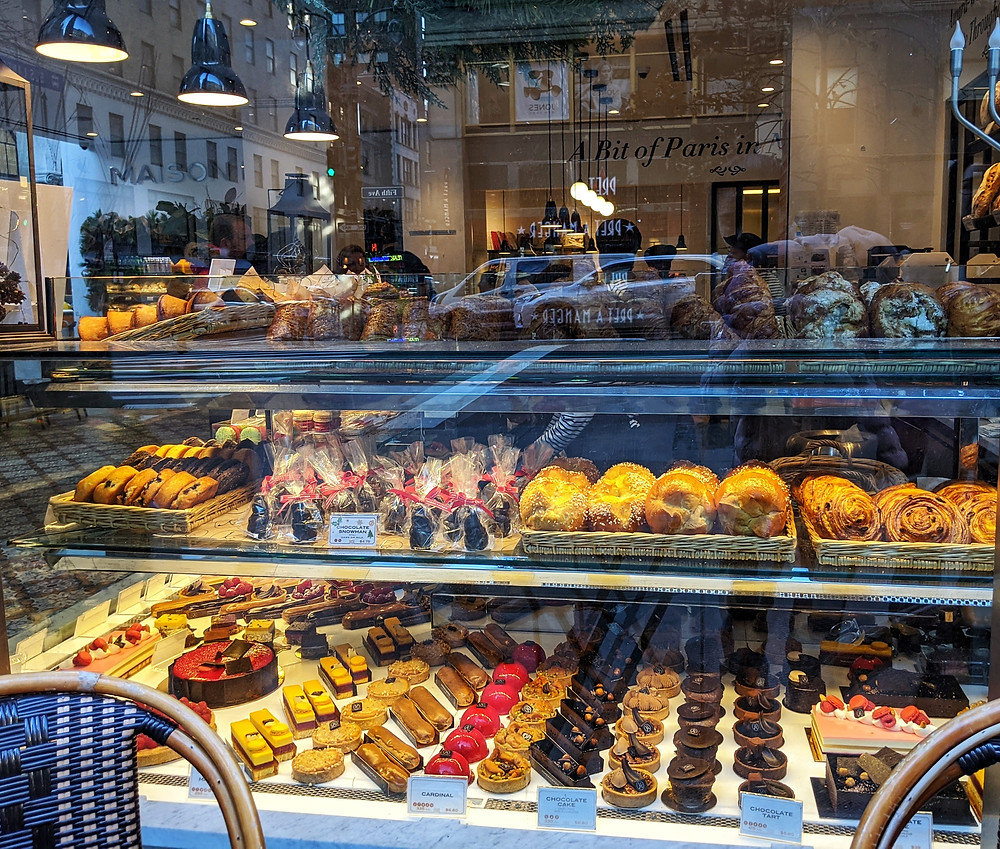 a-window-outside-a-bakery-with-rows-and-rows-of-pastries-and-breads