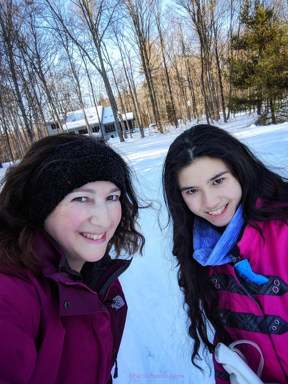 woman and teen girl in winter jackets with background of snowy woods and house in the distance