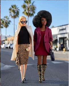 two fashion Barbie dolls one dressed in animal print pencil skirt with animal print purse coat and sunglasses with blonde hair the other with mini dress high boots, black purse wearing a mini dress with blazer over it