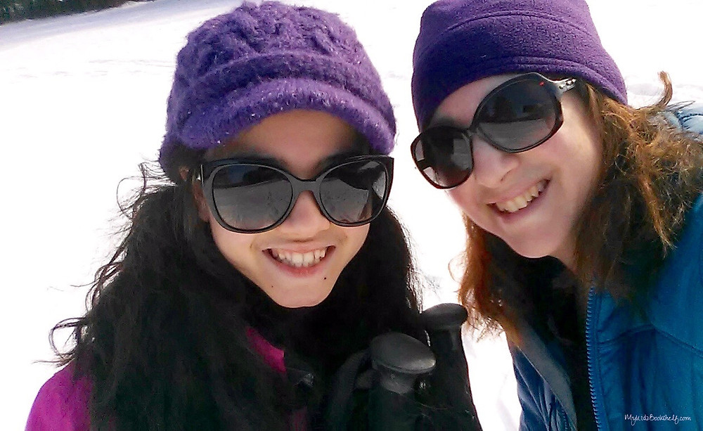 teen-girl-and-mom-wearing-sunglasses-and-hats-with-snowy-background