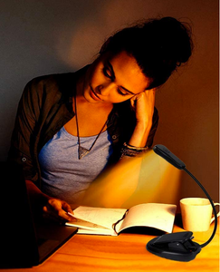 Book Light with young woman leaning on desk while reading with cup nearby