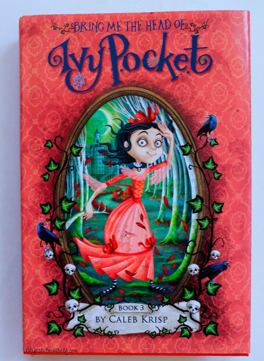 Illustration from book cover Bring Me The Head of Ivy Pocket by Caleb Krisp has girl on cover running through wooded area with big building in background with clocktower