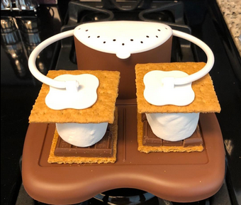 S'more maker device weighs down chocolate, graham cracker, marshmallow