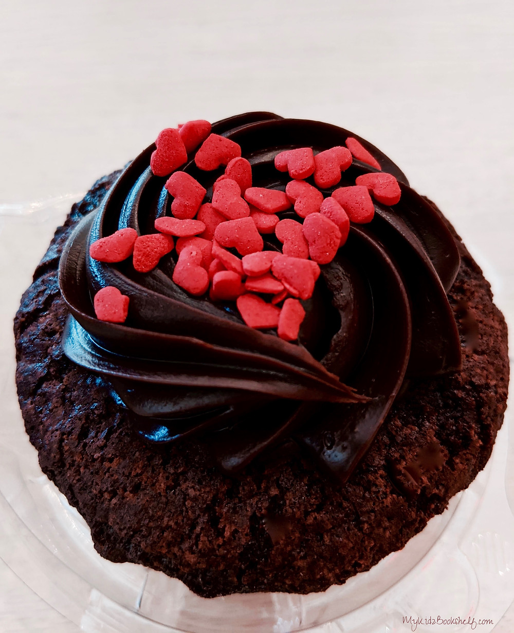 chocolate cupcake with chocolate frosting and red candy hearts