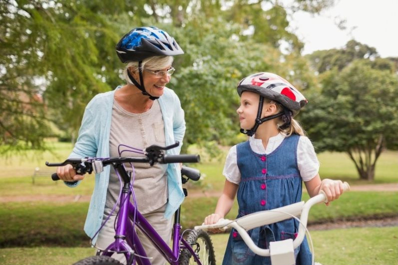Grandmother and young girl on their bikes wearing bike helmets