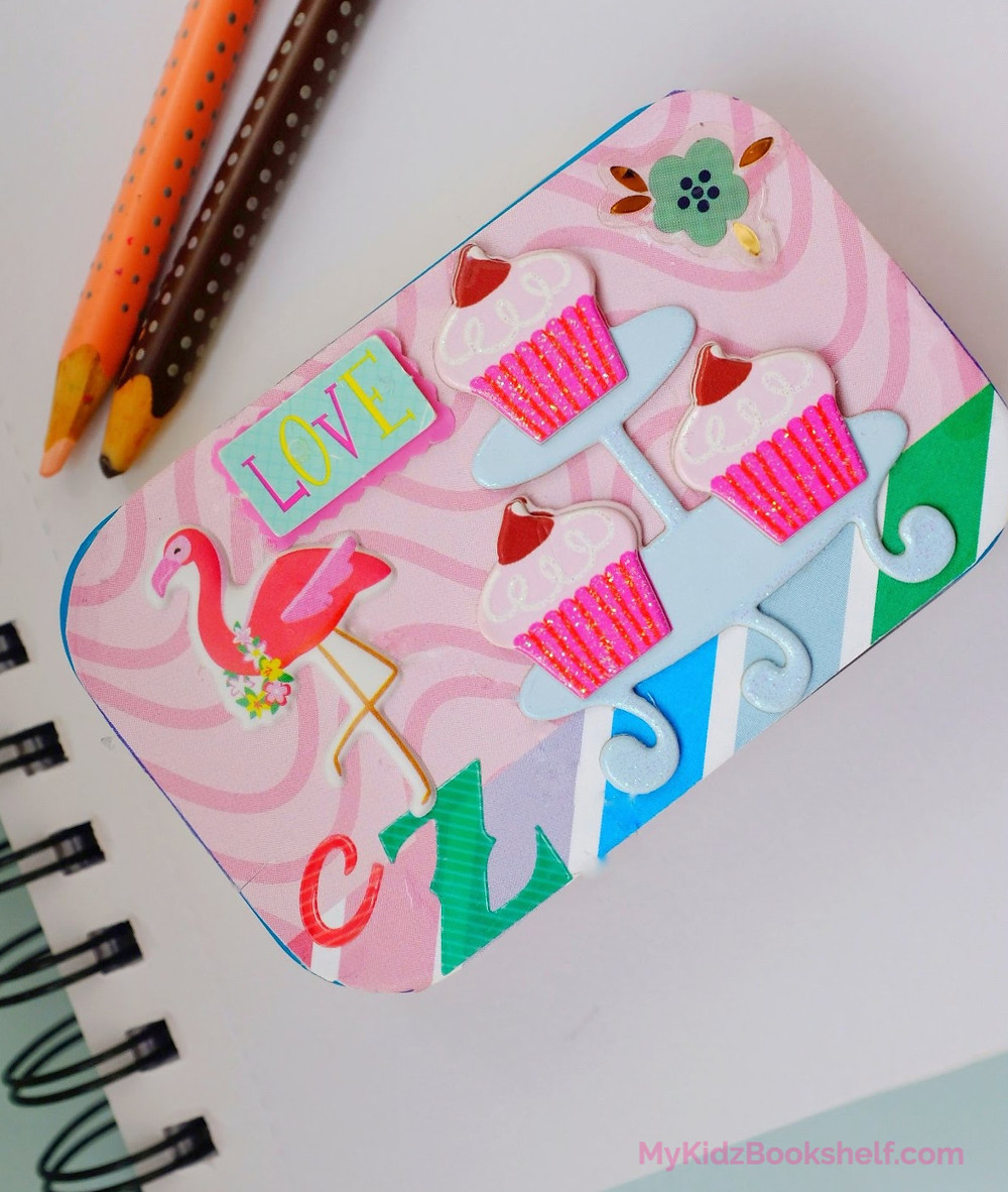 craft with Altoid tin decorated with papers, cupcake stickers, flamingo and table with notebook and colored pencils