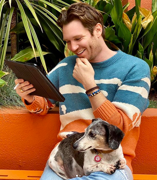 Oliver Gilmore the dachsund on Greg McGoon's lap while he reads outside