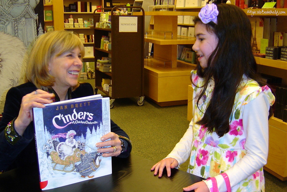 Jan Brett holding book Cinders talking to little girl