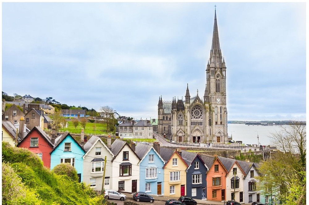 scene in Ireland with chruch and colorful houses on a hill next to the water