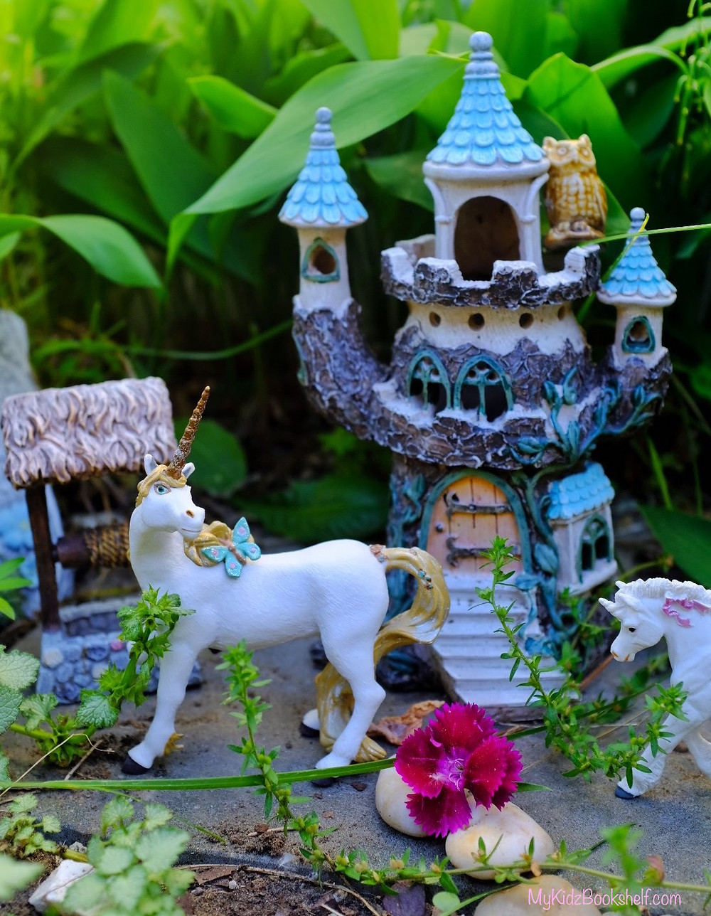 Fairy garden castle with unicorns, wishing well, flower surrounded by greenery