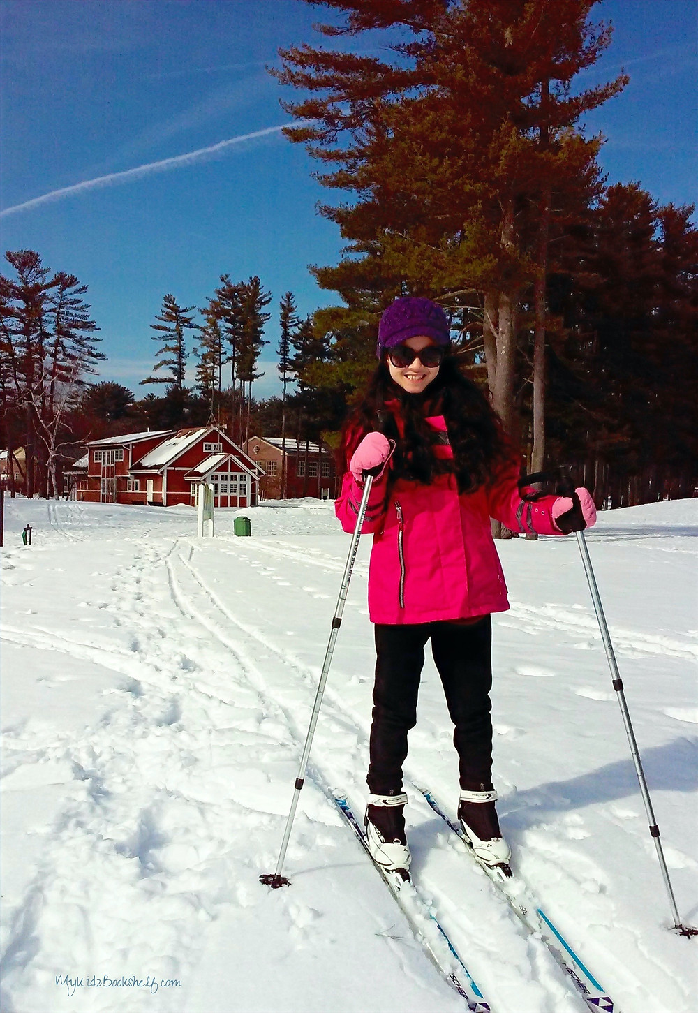 girl in snowy field cross country skiis with barn and trees behin