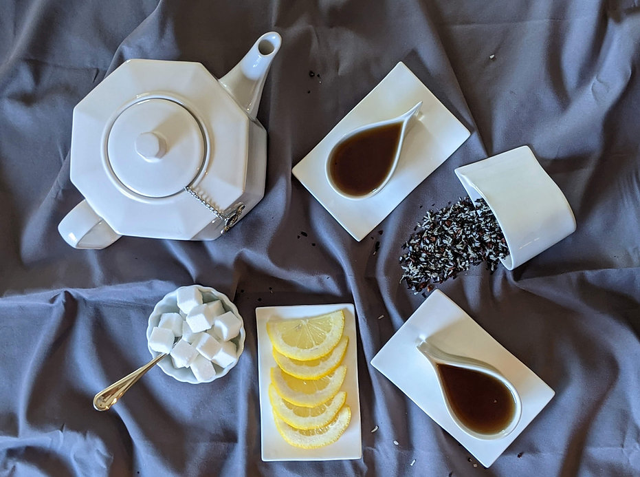 A tablescape of a teapot, teacups, spilled loose leaf tea, sugar bowl, and lemon slices