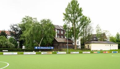 Spielfeld mit Häusern im Hintergrund