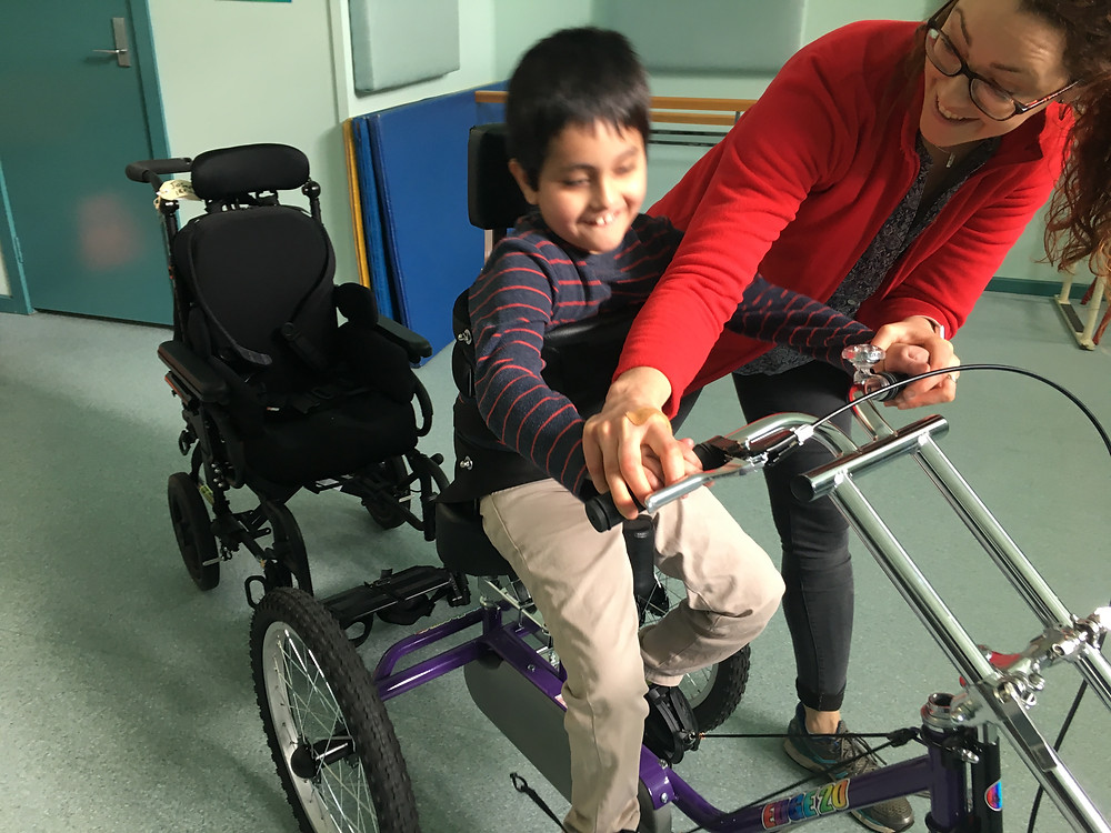 Child smiling in a custom tricycle assisted by a physio