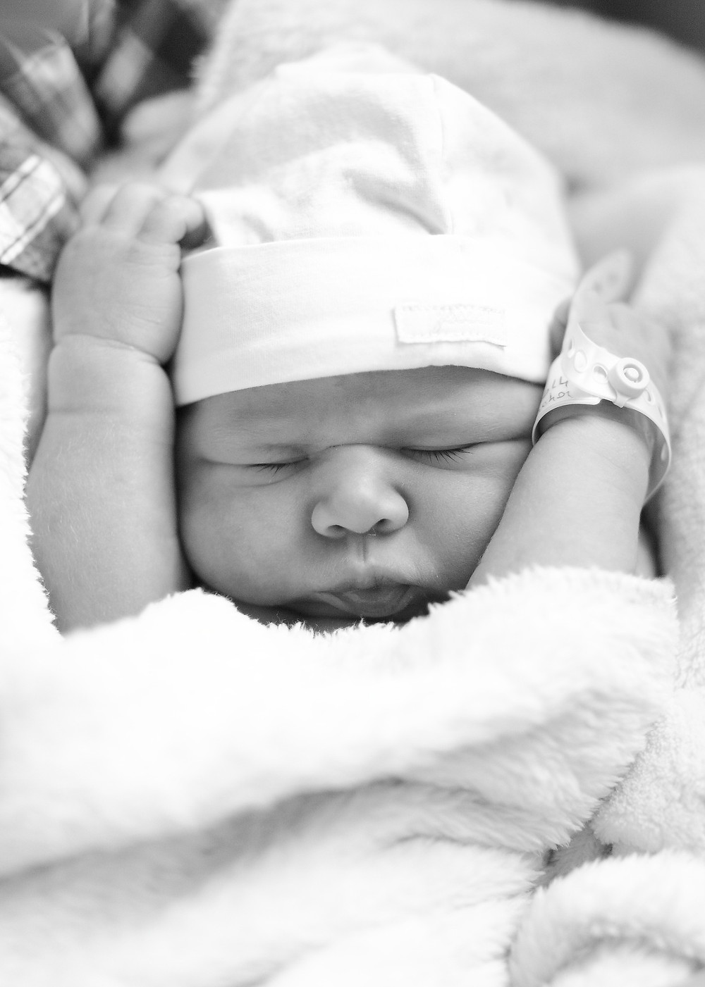 newborn baby wrapped up with hospital ID tag on wrist