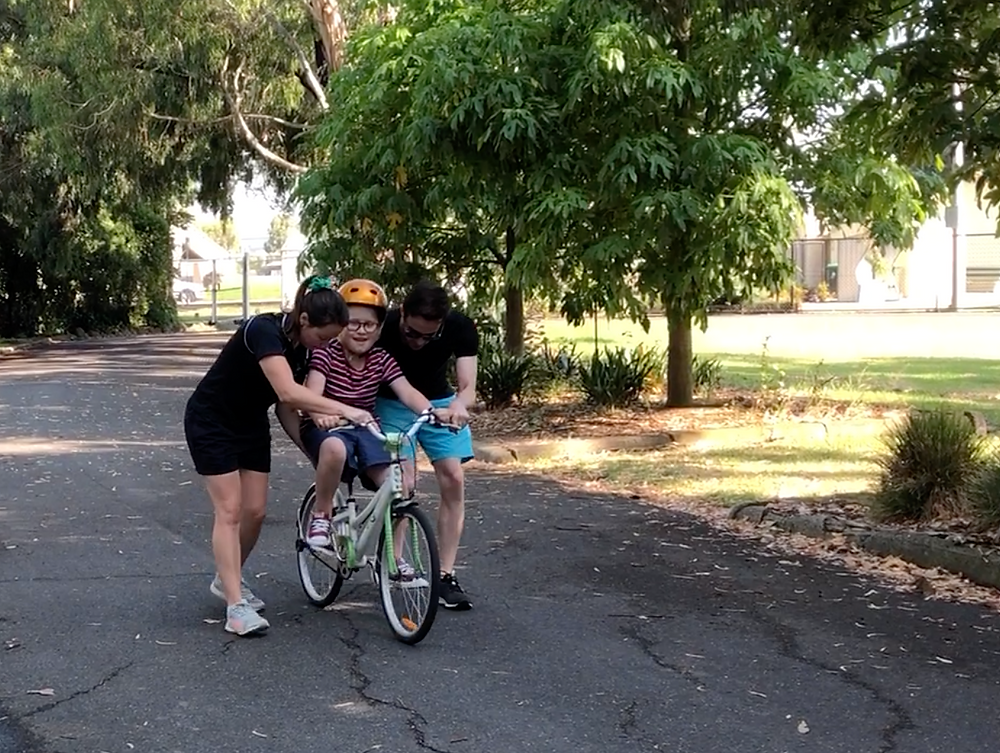 Child is assisted by two adults to ride a bike