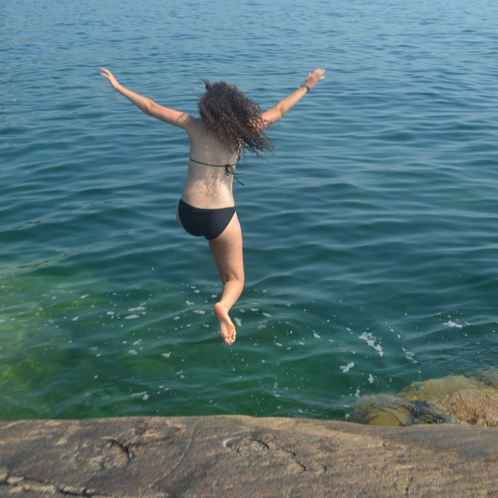 Image shows woman with dry hair and bathers jumping into the ocean off rocks. Source: Pixabay