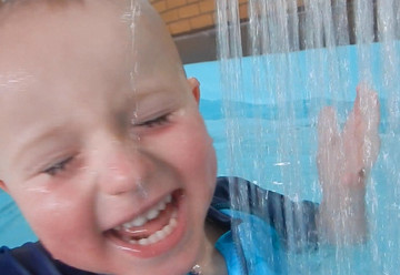 What bathtime games can help children get used to water on their face?