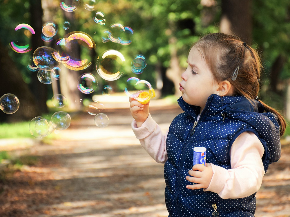 Child engaged in blowing bubbles outside