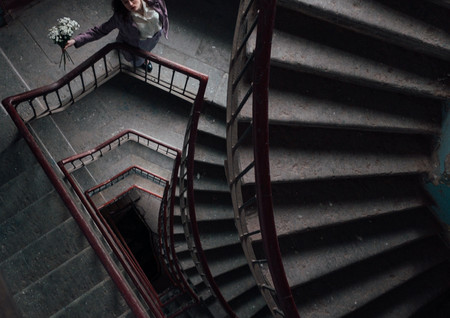 woman-standing-on-staircase-with-a-bouqu