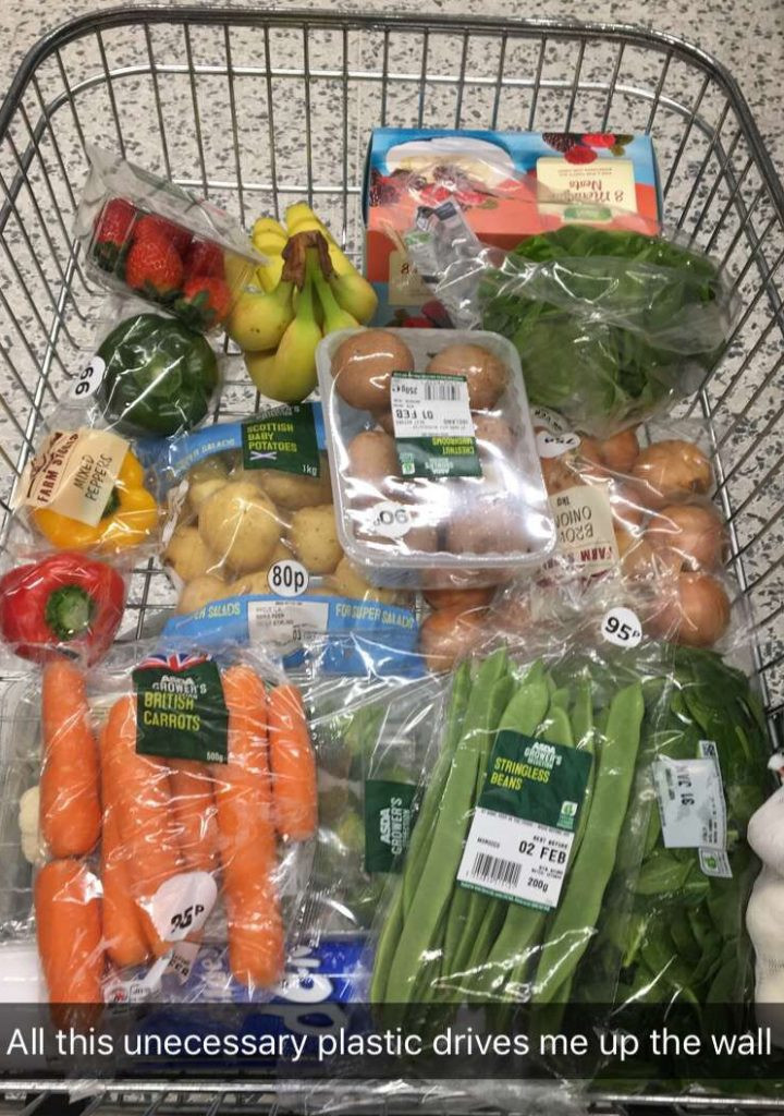 Shopping cart in Asda with veg wrapped in too much plastic