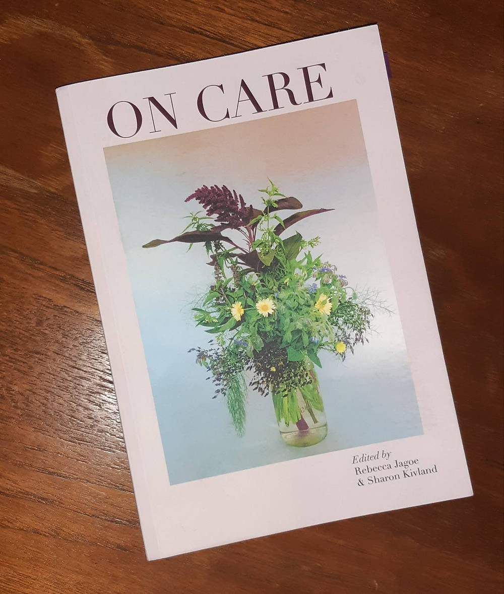The anthology ON CARE on a dark wooden table. The cover shows an image of a bouquet of medow flowers on a pastel pink-and-blue background, surrounded by a wide white margin, and the title in all caps,