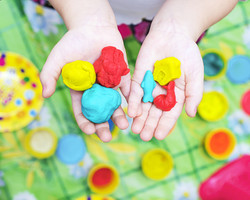 Child hands playing with colorful clay,