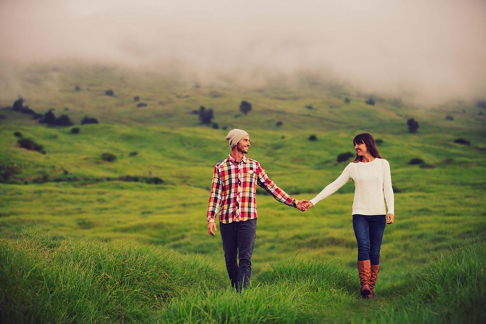 couple qui se tient par la main en plein champs