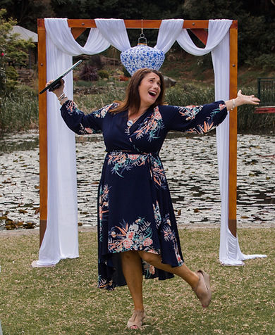 Laughing and smiling marriage celebrant standing next to a lily pond at Illawarra Rhonderdendron Gardens in NSW. Jo Booth. Event Celebrant and MC