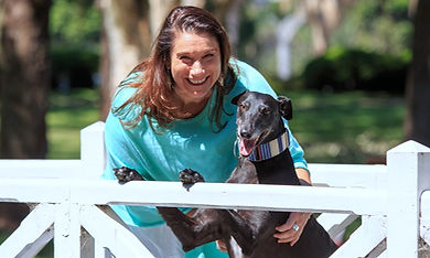 Smiling Jo Booth, Sydney marriage celebrant with her greyhound, Zia