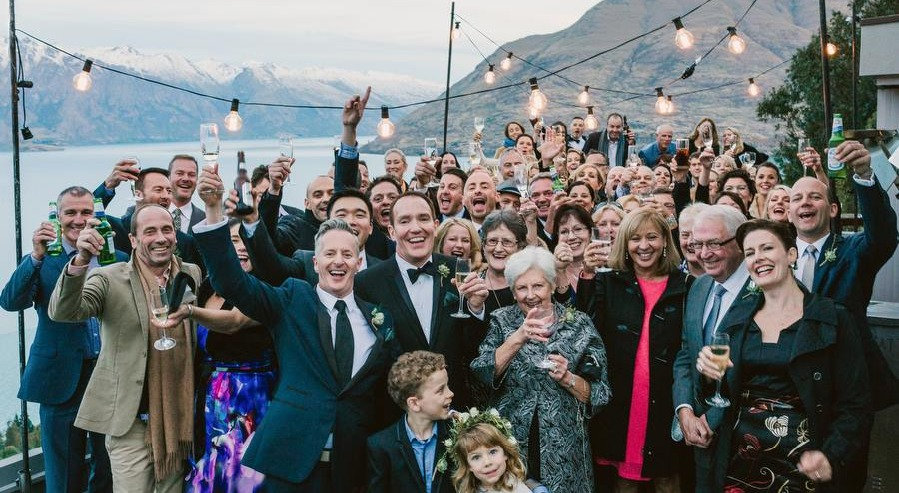 Wedding ceremony in Queenstown, New Zealand. Big wedding party with two grooms at the front all guests behind with glasses in the air.