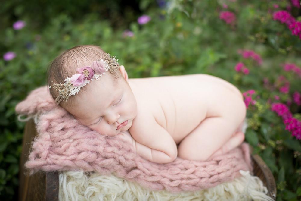 Newborn baby girl in field of flowers