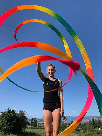 A rhythmic gymnast twirling colourful ribbon apparatus.