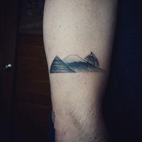 Minimal black and grey mountains tattoo at Baan Khagee Tattoo Chiang Mai