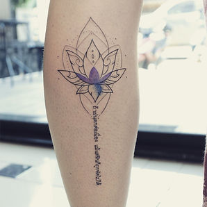 Best fine line lotus tattoo with Thai script by a tattooist in Chiang Mai, Thailand