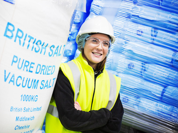 Portrait PR image of a young lady at salt factory wearing high visibility jacket and hard hat