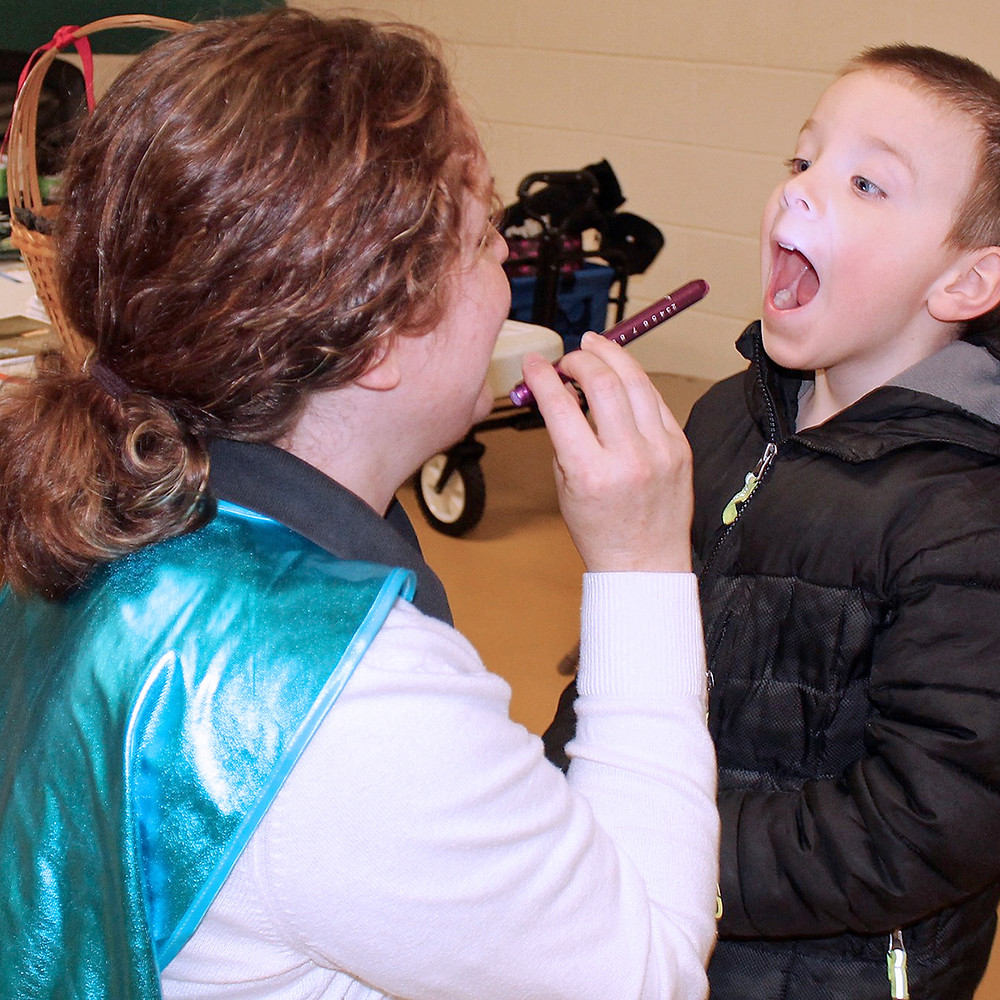 Young boy opens his mouth as a health professional checks his teeth at free health fair screening.