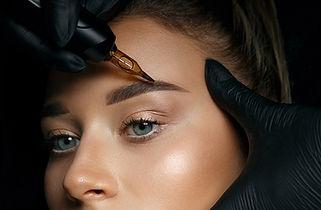 Beautician hand doing brow permanent mak