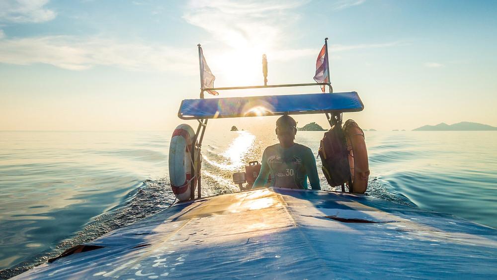 Thai gentleman steers a boat between islands of the Andaman