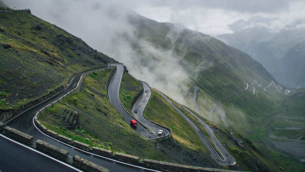 Mist and cloud rolls in over cars ascending Stelvio Pass in Italy's Alps
