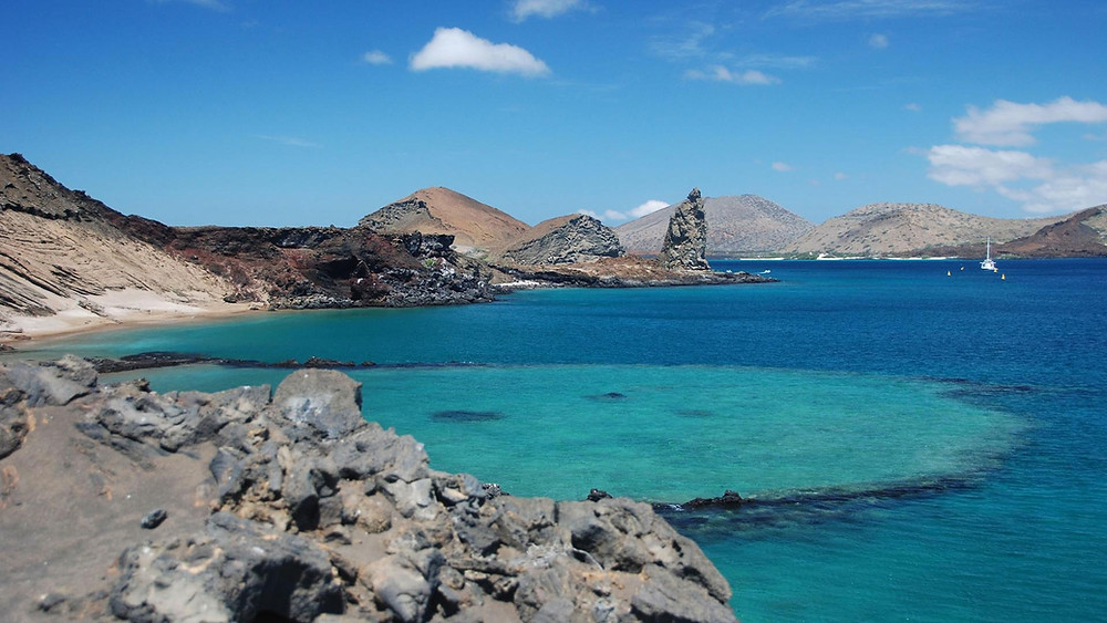 Blue waters of the Galapagos Islands with volcanic rock formations and landscape scenery under a blue sky