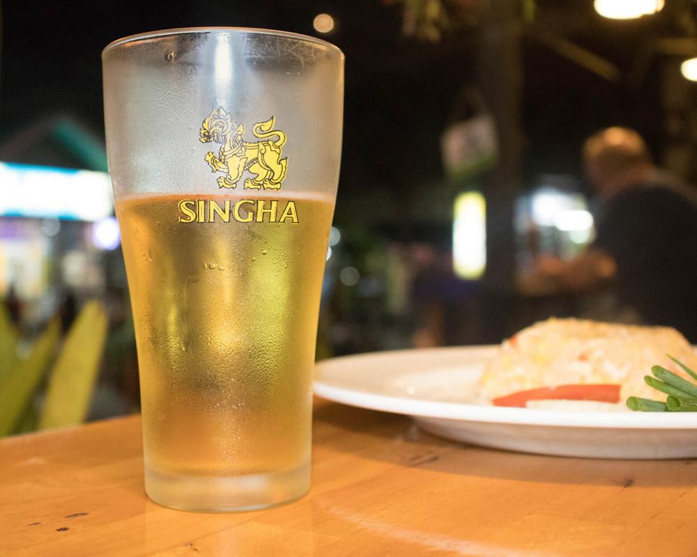 A half-full pint of Singha beer at a Thai restaurant