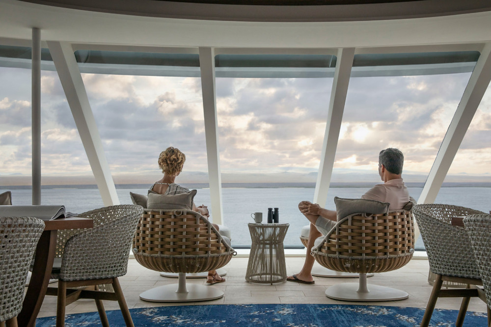 A couple look out over the landscapes of the Galapagos Islands from the Observation Deck on the Celebrity Flora